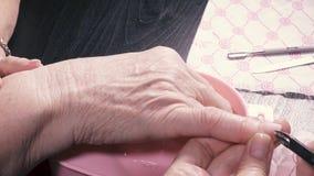 Pinça para remover a cutícula de uma mulher idosa video estoque