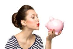 Pin女孩亲吻的piggybank 免版税库存照片