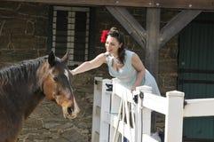 Pin вверх по девушке petting лошадь на ферме Стоковые Фотографии RF
