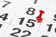 Pin на дате 15 Пятнадцатый день месяца отмечен с красной канцелярской кнопкой Pin на календаре стоковые фото