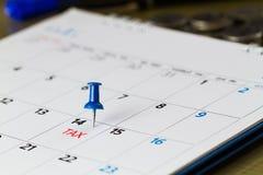 Pin на календаре на 14-ом из месяца с налогом текста и запачканной предпосылкой монеток Стоковое Изображение RF