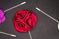 Pin отворотом ` s людей красной розы на черноте текстурировал изолированное матовое стоковая фотография