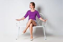 Pin acima da menina que senta-se no banco e no sorriso Fotos de Stock
