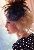 Pin-AP das Mädchen die Blondine in einem Hut mit einem Schleier gegen das Fenster in einem Profilschussabschluß oben Stockbilder