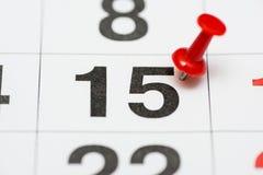 Pin auf dem Datum Nr. 15 Der fünfzehnte Tag des Monats wird mit roten Reißzwecken markiert Pin auf Kalender stockfotos
