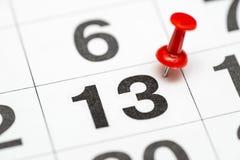 Pin auf dem Datum Nr. 13 Der Tag dreizehn des Monats wird mit roten Reißzwecken markiert Pin auf Kalender lizenzfreies stockbild