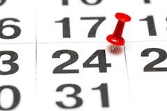Pin auf dem Datum Nr. 24 Der vierundzwanzigste Tag des Monats wird mit roten Rei?zwecken markiert Pin auf Kalender stockfoto