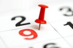 Pin auf dem Datum Nr. 9 9. Tag des Monats wird mit roten Reißzwecken markiert Pin auf Kalender stockfotografie