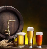 Pin of beer and glass of beer. Still life: old wooden pin of beer, glass of beer and wheat on the table in the cellar royalty free stock photography