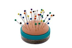 Pin Cushion. An isolated pin cushion and container with colourful pins Stock Photography