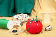 Pin cushion. A sewing table with buttons, pin cushion, tape measure and thimble stock images
