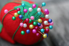 Pin cushion. Red pin cushion with colorful pins on stock photo