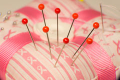 Pin Cushion. Item used by a Taylor pin cushion with red, yellow pins and needle with thread stock images