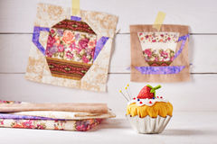 The pin cushion like a cupcake with strawberry and patchwork blocks of the cup and the teapot with a pattern of flowers Stock Photography