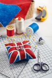 Pin cushion like Union Jack on white craft mat, sewing accessories stock photos