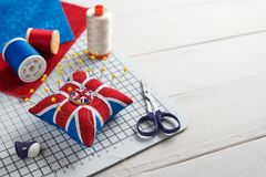 Pin cushion like Union Jack on white craft mat, sewing accessories stock image