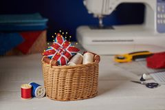 Pin cushion like Union Jack in a wicker basket, sewing machine, sewing accessories royalty free stock image