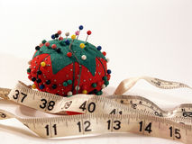 Pin cushion and measuring tape. Pin cushion and measureing tape on white royalty free stock image