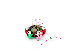 Pin cushion with pins. Pin cushion surrounded by fabric Chinese figures with pins Stock Images