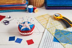 Pin cushion stylized elements of American flag, stacks of fabrics, quilting accessories stock photos