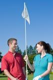 Pin di golf della holding della donna e dell'uomo - verticale Fotografie Stock Libere da Diritti