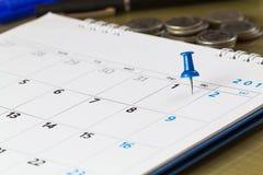 Pin en calendario en el 1r del mes con el fondo borroso de las monedas Imagen de archivo