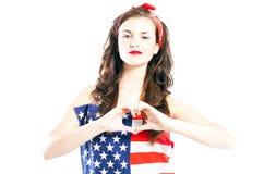 Pin encima de la muchacha envuelta en bandera americana con la mano en forma del corazón Foto de archivo