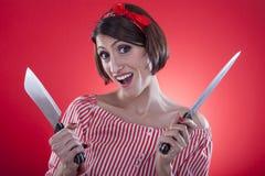 Pin encima de la muchacha que sostiene un cuchillo de cocina. Foto de archivo
