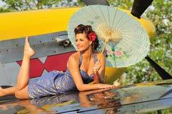 Pin herauf das Mädchen, das mit einem Weinlese-Kampfflugzeug aufwirft Lizenzfreies Stockfoto