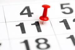 Pin na data número 11 O décimo primeiro dia do mês é identificado por meio de um percevejo vermelho Pin no calendário foto de stock
