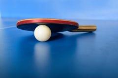 Pin pong球和红色桨在蓝色委员会 库存照片