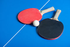 Pin pong ball and red paddle on blue board Royalty Free Stock Photos