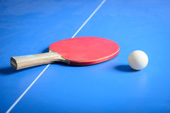 Pin pong ball and red paddle on blue board royalty free stock image