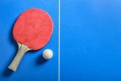 Pin pong ball and red paddle on blue board Royalty Free Stock Photography