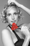 Pin up. The beautiful girl holds in hands a red sweet in the form of heart. A portrait of the girl-it it is black a white photo, a sweet brightly red. A photo in Royalty Free Stock Photography