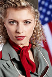 Pin-up army woman  standing near the American flag Stock Photos