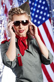 Pin-up army woman  standing near the American flag Stock Photography