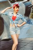 Pin up beautiful girl with red hair stands against the background of an old plane royalty free stock photo