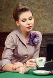 Pin Up beautiful young woman drinking tea in vintage interior Stock Photo