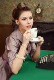 Pin Up beautiful young woman drinking tea in vintage interior Stock Photos