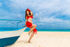 Pin up beautiful young woman in red bikini on a tropical beach. Stock Images