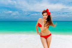 Pin up beautiful young woman in red bikini on a tropical beach. Royalty Free Stock Images