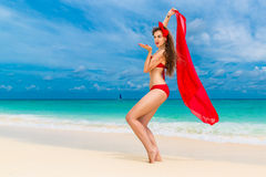 Pin up beautiful young woman in red bikini on a tropical beach. Royalty Free Stock Photo