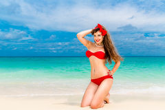 Pin up beautiful young woman in red bikini on a tropical beach. Stock Photos