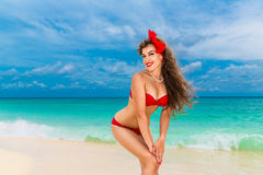 Pin up beautiful young woman in red bikini on a tropical beach. Stock Image