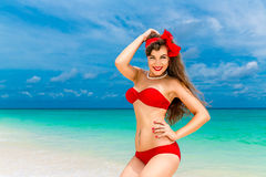 Pin up beautiful young woman in red bikini on a tropical beach. Stock Photography