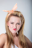 Pin up blonde fashion girl funny face. Pin up funny blonde fashion girl in hairband retro styling, woman making silly face, having fun, gray background Royalty Free Stock Photography