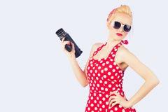 Pin-up con l'annata d'annata rossa della tenuta del vestito una macchina fotografica da 8 millimetri Immagini Stock