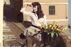 Pin-up d'annata con i fiori sulla bici in vecchia città Fotografie Stock Libere da Diritti