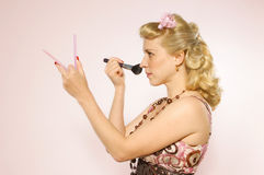 Pin-up gir doing make-up Stock Image